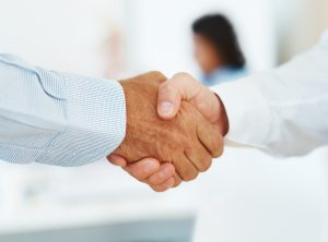 Closeup of a two businessman shake hands - Deal Confirmed